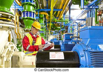 Engine room maintenance - Engineer looking aty a checklist ...