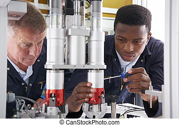 Engineer And Apprentice Working On Machine In Factory