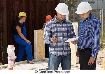Engineer and architect wearing hardhats standing discussing paperwork on a construction site with builders working behind them