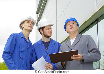 engineer and builders with hard hat using tablet outside building