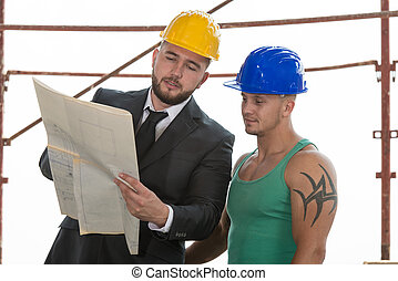 Engineer And Construction Worker Discussing A Project