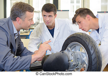 Engineer and students looking at wheel