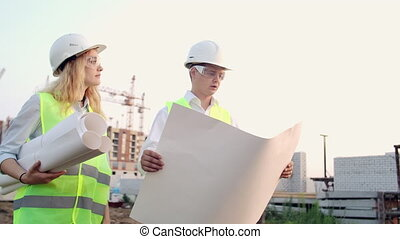 Engineer and supervisor go to the construction site to look at the drawings on the background of cranes and talk about work. Discussion with the contractor on the construction progress