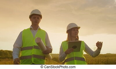 Engineer and supervisor with tablet PC and the drawings are...