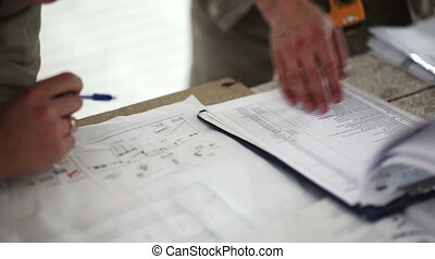 engineer and worker checking a list and blueprint work at the table