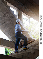 Engineer Architect working at Construction Site with blueprint