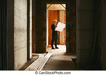 Engineer at work in construction site, standing in apartment building and looking at blueprints and plans
