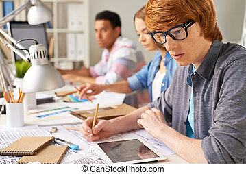 Portrait of pensive engineer making sketch on background of his colleagues