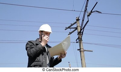 Engineer check electrical systems talk walkie-talkie, Inspector holding blueprints plan