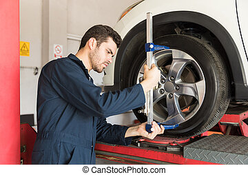 Maintenance engineer checking alignment of tire with camber caster adapter in garage