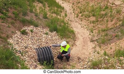 Engineer checking flow pipe in deep ditch