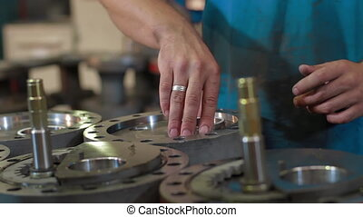 Engineer checks quality Parts of wellhead fittings and butterfly valves. Oil and Gas Wellhead tree equipment production plant. Worker in a factory is inspecting a product in manufactured industrial.