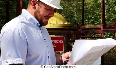 engineer checks the quality of the gas pipeline, talking on...