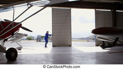 Male engineer closing hangar gate 4k