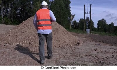 Engineer communicates near gravel pile