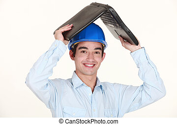 Engineer covering his head with a laptop