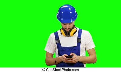 Engineer dials a message on his phone. Green screen