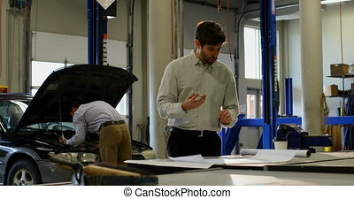 Front view of engineer discussing plans on mobile phone in workshop, with his coworker working on a car in the background
