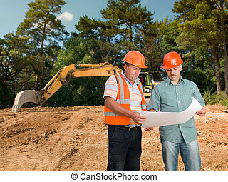 engineer discussing plan with construction worker