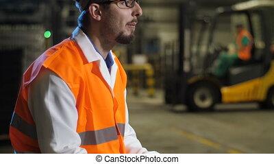 Engineer eating sandwich - Engineer in bright orange vest...