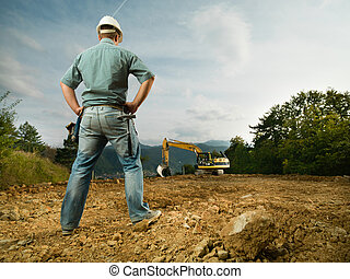 back view of male engineer standing on construction site evaluating the progress