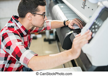 Engineer examining wide format printer