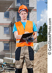 Engineer filling papers at building site