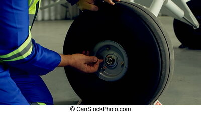 Engineer fixing a wheel of aircraft 4k - Engineer fixing a ...