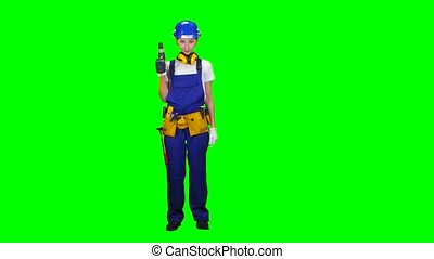 Engineer girl in a helmet and overalls holds a drill in her hands . Green screen