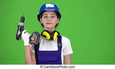 Engineer girl in a helmet and overalls holds a drill in her hands . Green screen. Slow motion. Close up