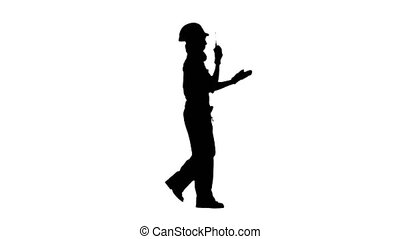 Engineer girl in glasses is walking along the street and talking on the walkie talkie . Silhouette. White background. Side view