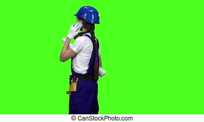 Engineer girl standing with her back holding a drawing and talking on the phone . Green screen. Slow motion. Back view