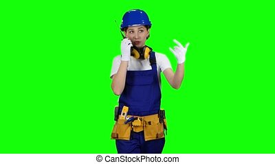 Engineer girl wearing glasses and wearing a blue helmet goes along the street and talks on the walkie talkie. Green screen