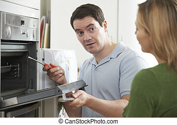 Engineer Giving Woman Advice On Kitchen Repair