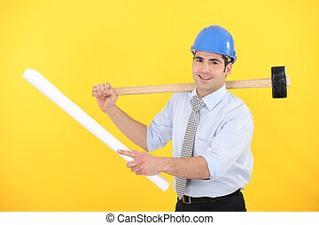 Engineer holding a rolled-up blueprint and a mallet