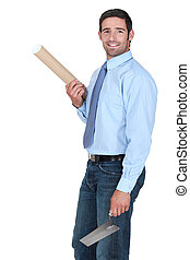 Engineer holding a rolled-up plan and a trowel