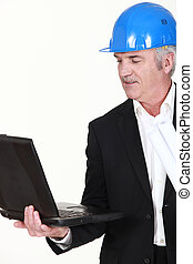Engineer holding his laptop and rolled-up drawings