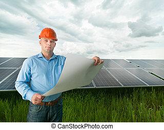 engineer holding solar panel station plan