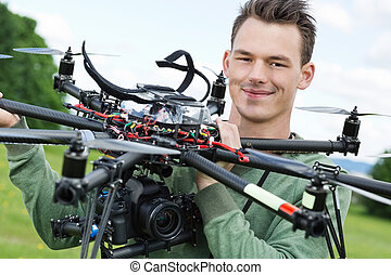 Engineer Holding UAV With Camera - Portrait of confident...