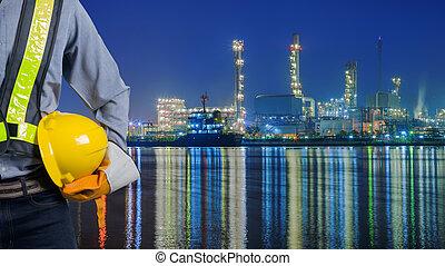 Engineer holding yellow helmet with oil refinery. - Engineer...