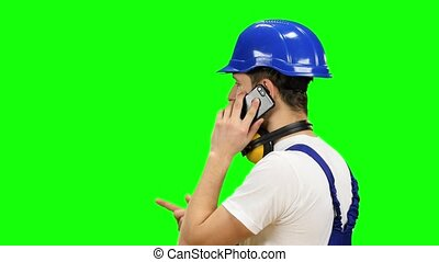Engineer in a blue helmet speaks on the phone and shows a thumbs up. Green screen