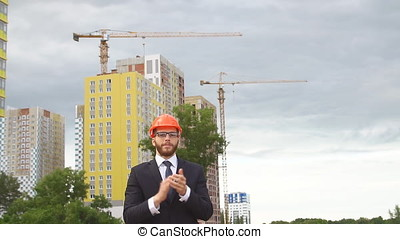 Engineer in a business suit on a construction site. Slow motion