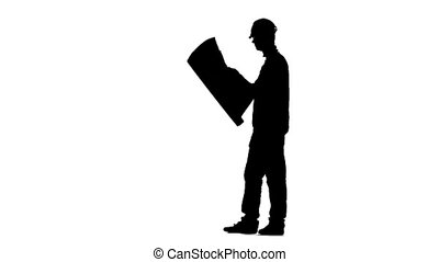 Engineer in a helmet holds a drawing of the building in his hands. Silhouette. White background. Slow motion