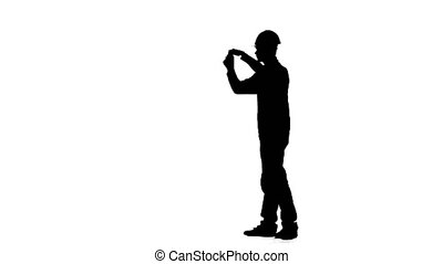 Engineer in a helmet measures roulette measurements for the drawing. Silhouette. White background