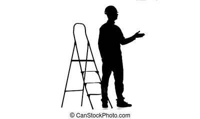Engineer in a helmet stands near the stepladder. Silhouette. White background. Slow motion