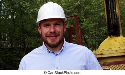 engineer in a white helmet smiling - engineer in a white...