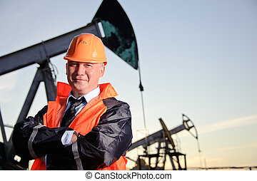 Engineer in an Oil field - Oil worker in orange uniform and ...