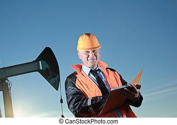 Engineer in an oil field - Oil worker in orange uniform and ...