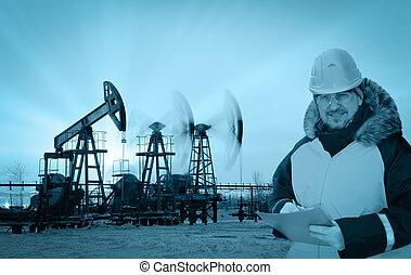 Engineer in an oil field - Oil worker in orange uniform and...