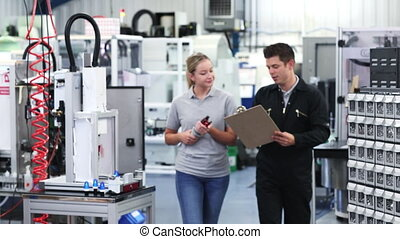 Engineer In Factory Discussing Component With Female...
